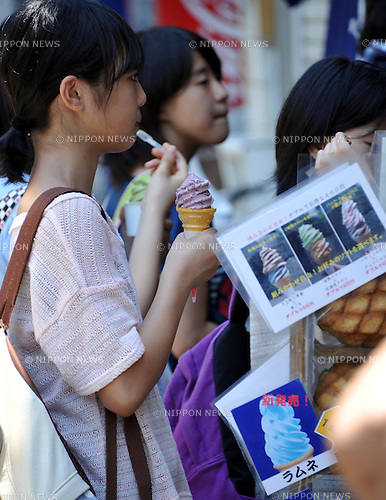 July 12th, 2011, Tokyo, Japan - Visitors to Sensoji Buddhist Temple in downtown Tokyo cool themselves off with cones of ice cream parlor as the mid-afternoon temperature hits 32 degrees Celsius (89 degrees Fahrenheit) on Tuesday, July 12th, 2011.The Japanese government warned the public not to cut back too much on the use of air conditioners in the midst of national drive to conserve energy, citing the possibility of heat stroke. Nearly 7,000 people were hospitalized for heat exhaustion in June, three times more than last year. Weather officials said June's heat wave sent the mercury rising in parts of Japan to their highest levels since 1961. Temperatures in downtown Tokyo reached 35 degrees Celsius (95 degrees Fahrenheit) on June 29 - the third highest in June since the Meteorological Agency began compiling comparable records in 1875. (Natsuki Sakai/AFLO)