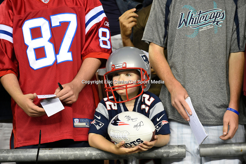 August 1, 2014 - Foxborough, Massachusetts, U.S.- A young fans waits to have his football autographed during the New England Patriots training camp held at Gillette Stadium in Foxborough Massachusetts.  Eric Canha/CSM