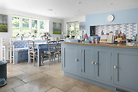 A pale blue and white bespoke country kitchen by Parlour Farm Kitchens with stone flagged flooring and a bespoke banquette by Moulder Joinery