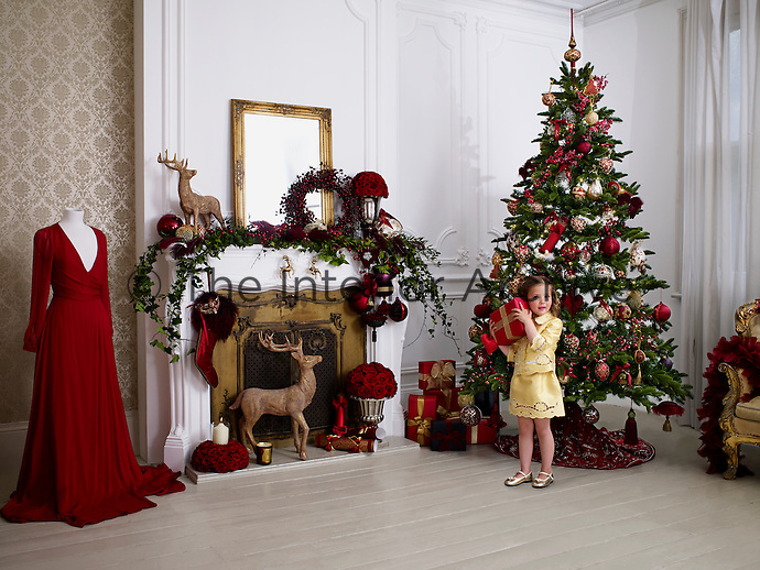 Interior in location house, London. Christmas scene with decorations, a mantelpiece, a highly decorated Christmas tree and a girl holding a gift. The colours are quite dark and red dominates the overall scene.