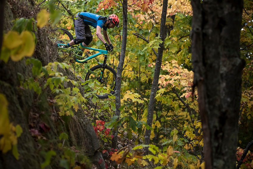 Trail builder Nic Dobbs samples the signature natural wall ride on his trail Doc Nobbs at Harlow Lake near Marquette, Michigan.