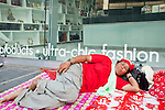"""Apr 4, 2010 - BANGKOK, THAILAND: Red Shirt protestors sleep in front of high end fashion stores in the Chidlom area of central Bangkok Sunday, Apr. 4. Thousands of members of the United Front of Democracy Against Dictatorship (UDD), also known as the """"Red Shirts"""" and their supporters moved their anti government protests into central Bangkok Apr. 4 when they occupied Ratchaprasong intersection, the site of Bangkok's fanciest shopping malls and several 5 star hotels. The Red Shirts are demanding the resignation of current Thai Prime Minister Abhisit Vejjajiva and his government. The protest is a continuation of protests the Red Shirts have been holding across Thailand. They support former Prime Minister Thaksin Shinawatra, who was deposed in a coup in 2006 and went into exile rather than go to prison after being convicted on corruption charges. Thaksin is still enormously popular in rural Thailand. This move, away from their traditional protest site in the old part of Bangkok, has gridlocked the center of the city and closed hundreds of stores and restaurants and several religious shrines. There has not been any violence, but the government had demanded that the Red Shirts return to the old part of the city.   PHOTO BY JACK KURTZ"""