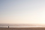 Woman walking along ocean beach alone in tranquil scene