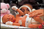 Neonatology unit, nurse cares for premature infant in incubator