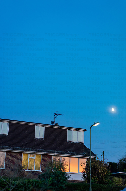 Bungalow built in the 1960s at dusk wi the moon