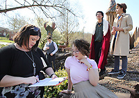 NWA Democrat-Gazette/DAVID GOTTSCHALK Andrea Broshears (from left), the drama teacher at Haas Hall Academy, reviews the script Thursday, April 12, 2018, for Rumpelstiltskin, Private Eye with Ethan Bell, a freshman, Lucinda Williams, a senior, Javian Walter, a senior, and Mark Moghadam, a senior, before they act out a wedding scene at Wilson Park in Fayetteville. The students are filming a movie as part of their final semester performance.