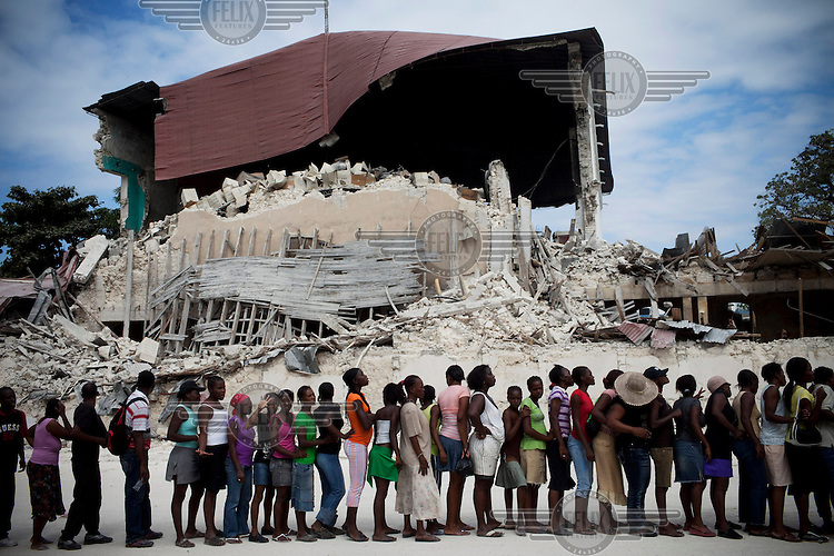 People queueing for distribution of food aid by the United Nations World Food Programme (UN WFP) in front of a building devastated by the earthquake..A 7.0 magnitude earthquake struck Haiti on 12/01/2010. Early reports indicated that more than 100,000 may have been killed and three million affected.