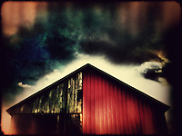 Red siding on old barn with stormy sky. iPhone photo.