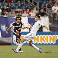 New England Revolution defender Kevin Alston (30) clears the ball as Vancouver Whitecaps FC midfielder Omar Salgado (17) pressures. In a Major League Soccer (MLS) match, the New England Revolution defeated Vancouver Whitecaps FC, 4-1, at Gillette Stadium on May 12, 2012.
