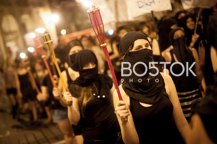 "Face covered women march during the demonstration with torch flames. Iruñea - Pamplona  (Basque Country) July 4, 2015. Some feminist groups called for a demonstration with the slogan ""fear will switch sides"", demanding women should freely enjoy streets and nights, and to condem sexist violence. (Gari Garaialde / BostokPhoto)"