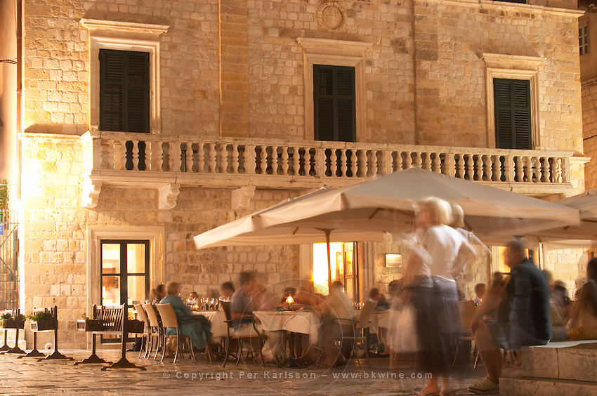a restaurant with outside seating on the terrace on the Gunduliceva Poljana square in the evening at night with street lights Dubrovnik, old city. Dalmatian Coast, Croatia, Europe.