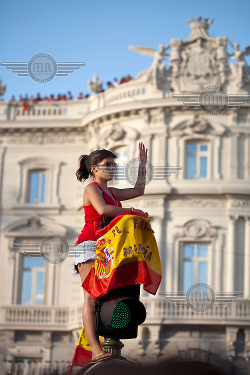 A young woman holds the national flag on top of traffic lights during the victory parade of the Spanish national football team who won the UEFA EURO 2012 competition.