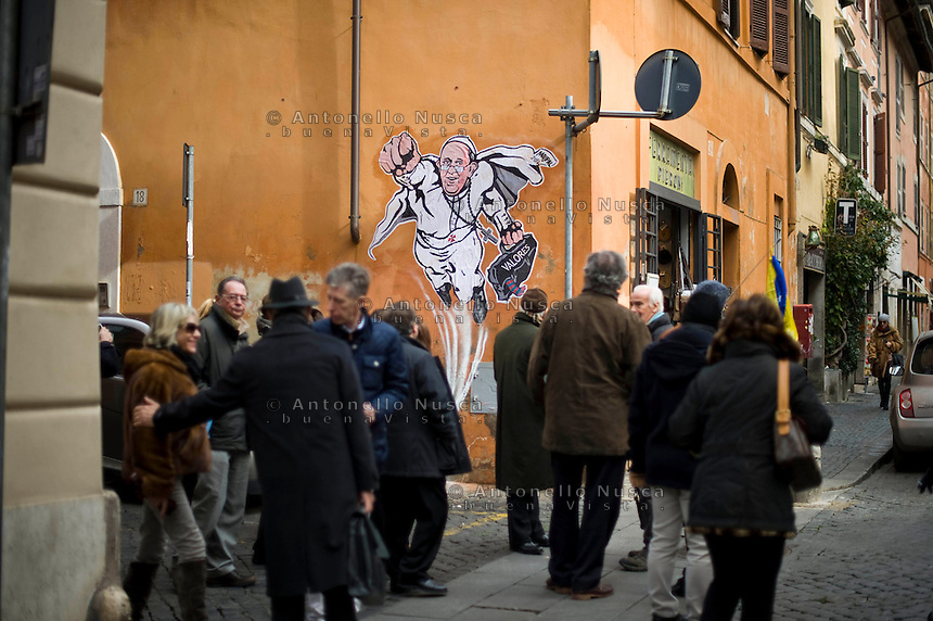 Alcune persone passano davanti l'opera dell'artista di strada Mauro Pallotta che ritrae Papa Francesco nelle vesti di un supereroe. People walk past a graffiti featuring a 'superhero' version of Pope Francis appears in Borgo Pio, next to St. Peter's Square  in Rome. The image started circulating from the twitter account of the Vatican and has rapidly spread around the world.