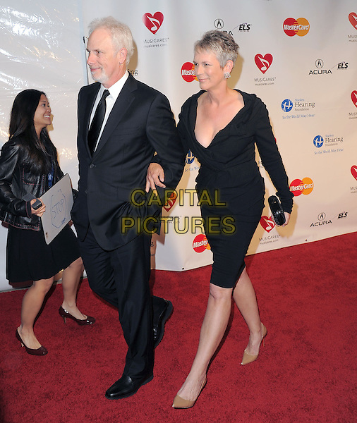 CHRISTOPHER GUEST & JAMIE LEE CURTIS .at The 2011  MusiCares Person of the Year Dinner at the Los Angeles Convention Center, West Hall in Los Angeles, California, USA, .February 11th 2011..full length black dress black dress suit tie  suit tie couple walking .CAP/RKE/DVS.©DVS/RockinExposures/Capital Pictures.