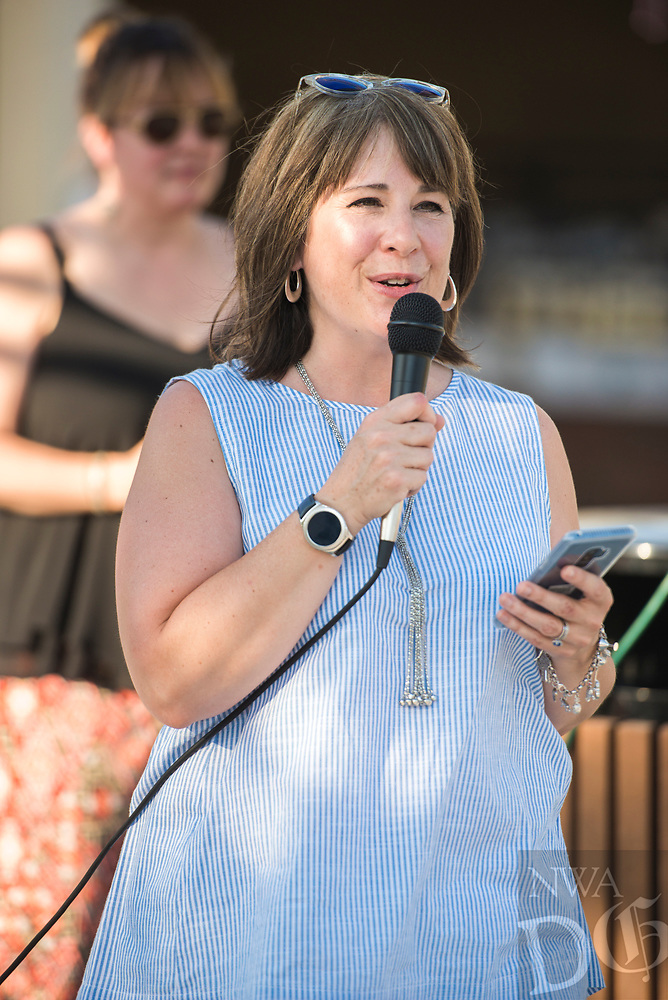 NWA Democrat-Gazette/CHARLIE KAIJO Kelly Syer, executive director of the Downtown Springdale Alliance, speaks to dinner guests, Saturday, June 9, 2018 on Emma Ave. in Springdale. &quot;This is all about community, bringing people together who know each other and don&acirc;&euro;&trade;t know each other, sitting down for a delicious meal and enjoying and celebrating community,&quot; she said. <br />
