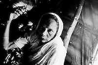 60-year-old Hanifa has been sick for weeks and has no family members to take care of her. Unable to receive medical assistance she relies on other Rohingya to help her make it from one day to the next. (2009)