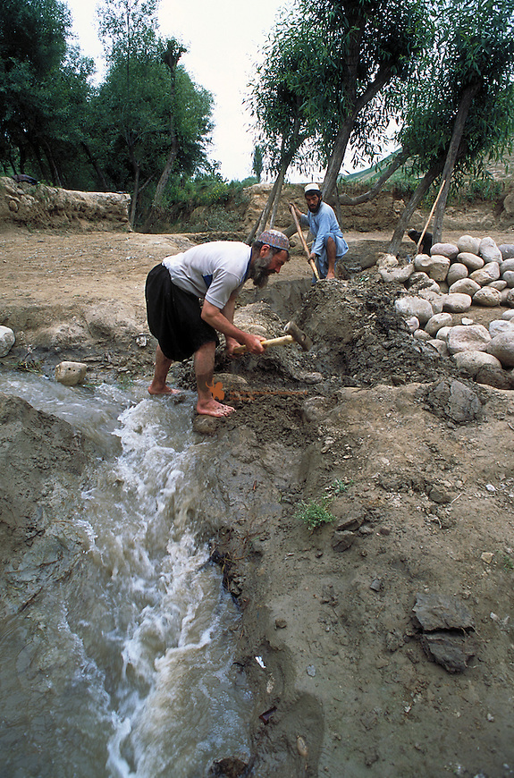Farmer repairing damaged irrigation channel