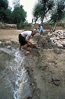 Farmer repairing damaged irrigation channel