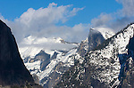 El Capitan in shadow; Half Dome and Clouds Rest covered with snow; clouds in the blue sky.