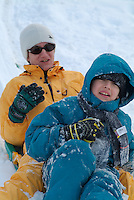 Mother and son on a sled at a ski resort in the French Alps, France.