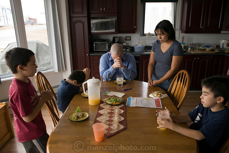 """The Melanson family prays before lunch in Iqualuit, Canada. Iqaluit, with a population of 6,000, is the largest community in Nunavut as well as the capital city. It is located in the southeast part of Baffin Island. Formerly known as Frobisher Bay, the town is at the mouth of the bay of that name, overlooking Koojesse Inlet. """"Iqaluit"""" means 'place of many fish'. Canada. The image is part of a collection of images and documentation for Hungry Planet 2, a continuation of work done after publication of the book project Hungry Planet: What the World Eats, by Peter Menzel & Faith D'Aluisio."""