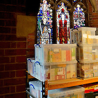 A stained glass window depicts Jesus, now obscured by towers of boxes inside Hammersmith and Fulham food bank in Christ Church, Fulham. Volunteers meet customers, offering a hot drink and cake before an interview is carried out to assess the person's needs. After this specially-selected bags of food are made up. Many food banks are run in or by local churches though not all volunteers at this bank would describe themselves as regular church goers.