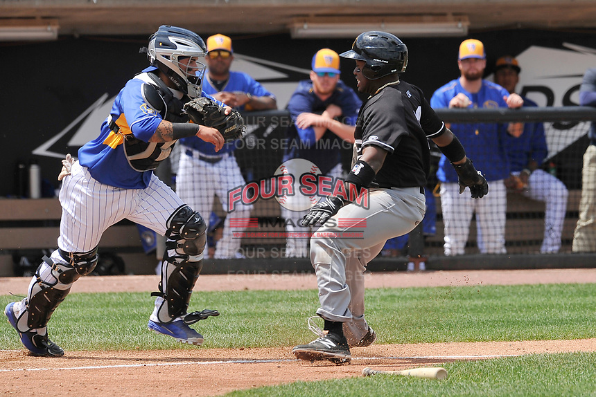Wisconsin Timber Rattlers catcher Mario Feliciano (4) chases down Quad Cities Ronnie Dawson (12) near home plate during a game against the Quad Cities River Bandits at Fox Cities Stadium on June 27, 2017 in Appleton, Wisconsin.  Wisconsin lost 6-5.  (Dennis Hubbard/Four Seam Images)