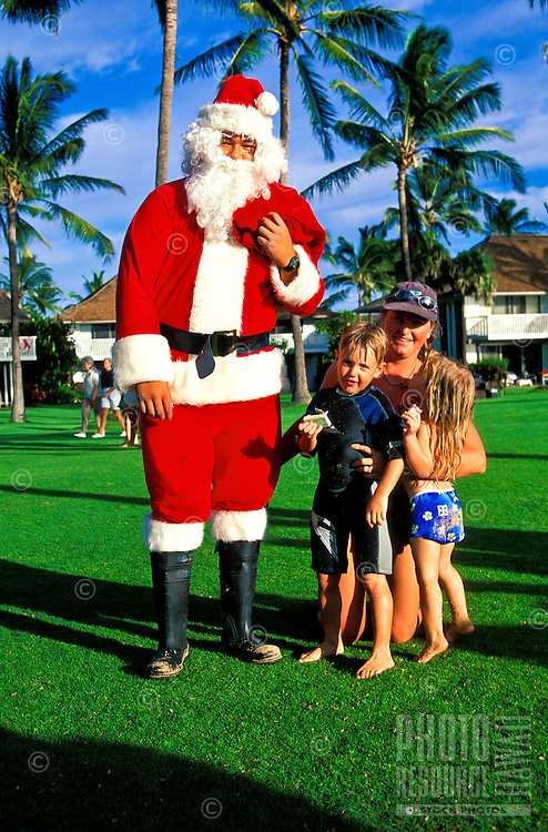 On a large grassy lawn on the south side of Kauai, a man dressed as Santa Claus stands near a woman and two young children