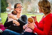 "A midwife, using a doll to demonstrate, discusses breastfeeding techniques with a young woman at a drop-in breastfeeding support centre.<br /> <br /> Image from the breastfeeding collection of the ""We Do It In Public"" documentary photography picture library project: <br />  www.breastfeedinginpublic.co.uk<br /> <br /> Hampshire, England, UK<br /> 13/03/2013<br /> <br /> © Paul Carter / wdiip.co.uk"