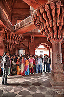 Fatehpur Sikri, Uttar Pradesh, India.  Indian tourists Viewing the Throne Pillar in the Diwan-i-Khas (Hall of Private Audience).