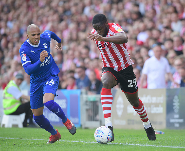 Lincoln City's John Akinde vies for possession with Tranmere Rovers' Jake Caprice<br /> <br /> Photographer Chris Vaughan/CameraSport<br /> <br /> The EFL Sky Bet League Two - Lincoln City v Tranmere Rovers - Monday 22nd April 2019 - Sincil Bank - Lincoln<br /> <br /> World Copyright © 2019 CameraSport. All rights reserved. 43 Linden Ave. Countesthorpe. Leicester. England. LE8 5PG - Tel: +44 (0) 116 277 4147 - admin@camerasport.com - www.camerasport.com
