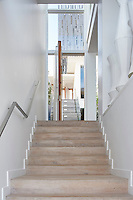 A wooden staircase lead up to the front entrance of a contemporary beach house.