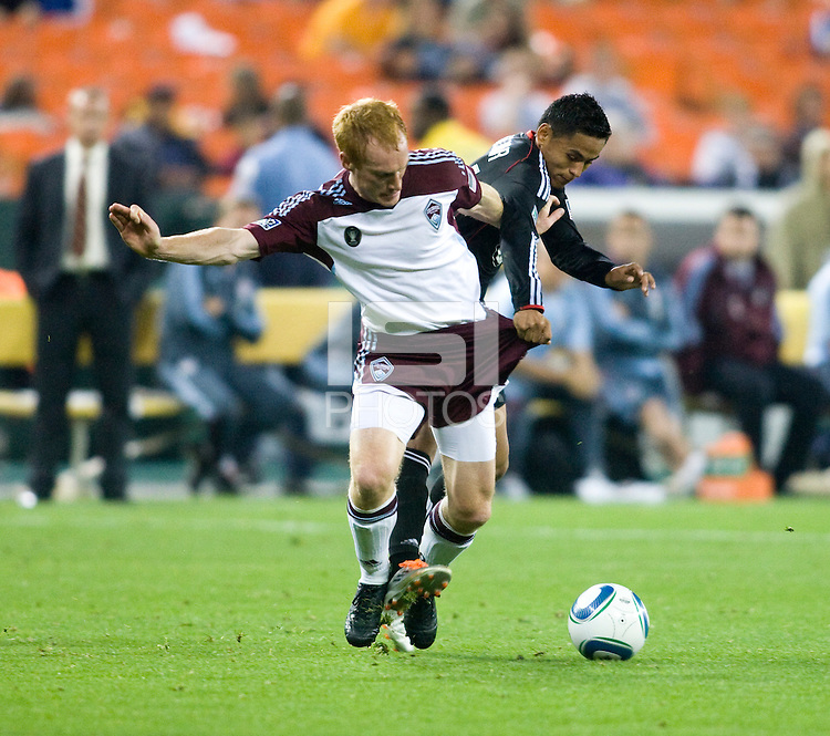 Andy Najar (14) of D.C. United fights for the ball with Jeff Larentowicz (4) of the Colorado Rapids during the game at RFK Stadium in Washington, DC.  D.C. United tied the Colorado Rapids, 1-1.