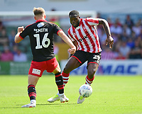 Lincoln City's John Akinde vies for possession with Swindon Town's Martin Smith<br /> <br /> Photographer Chris Vaughan/CameraSport<br /> <br /> The EFL Sky Bet League Two - Lincoln City v Swindon Town - Saturday 11th August 2018 - Sincil Bank - Lincoln<br /> <br /> World Copyright &copy; 2018 CameraSport. All rights reserved. 43 Linden Ave. Countesthorpe. Leicester. England. LE8 5PG - Tel: +44 (0) 116 277 4147 - admin@camerasport.com - www.camerasport.com