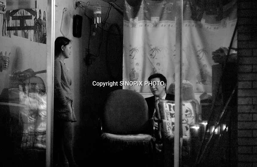 Prostitites wait for clients in a hairdressing salon and massage parlour that is cover for a brothel in chengdu the capitol of sichuan Province in western China.  the city has well over a thousand such brothels.