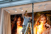 Steve Cox, from Maple Ridge, BC  takes measurements to board up a vandalized window at the H & M store in downtown Vancouver, BC on June 16, 2011.  Working for Extreme Glass, a co-worker estimated they have orders to board up around 70 storefronts. Rioters looted stores and burned cars after the Canucks' loss to the Boston Bruins in last night's Stanley Cup.  (photo copyright Karen Ducey 2011)