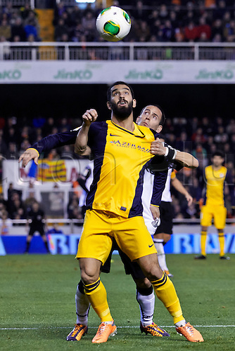 07.01.2014 Valencia, Spain. Midfielder Arda Turan of Atletico Madrid (L) challenges for the ball with Defender Joao Pereira  of Valencia CF  during the Copa del Rey Game between Valencia and Atletico de Madrid at Mestalla Stadium, Valencia