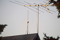 LIGHTNING ROD<br /> Lightning rod on wooden roof next to television antenna. Lightning rods form a low-resistance path for the lightning  discharge and prevent it from traveling through the structure
