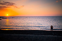 A couple share an embrace at sunset on a camping beach in Kailua-Kona, Big Island.