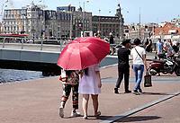 Nederland - Amsterdam - 2018.  Zomer in Amsterdam. Toeristen lopen met een paraplu in de zon.  Foto Berlinda van Dam / Hollandse Hoogte.