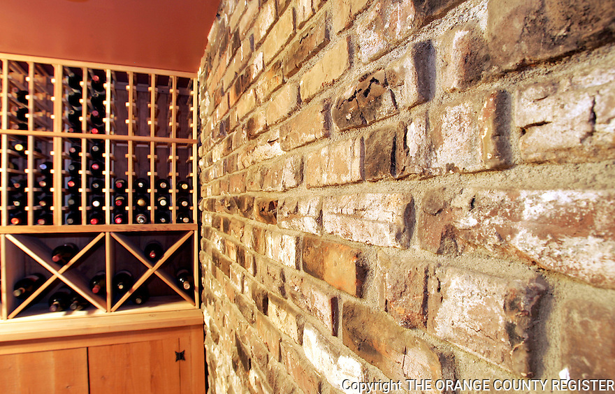 When the current owners rebuilt this 1906 Craftsman style home in Seal Beach from the ground up, they rebuilt it almost identical to the original.  However, they did add this wine cellar and incorporated some of the original chimney bricks onto one of the walls.<br />
