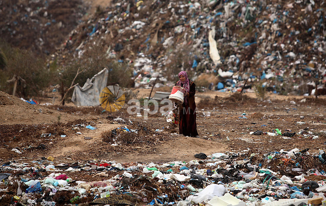 A Palestinian woman removes rubbish outside her dwelling in Khan Younis in the southern Gaza Strip December 19, 2016. Photo by Ashraf Amra