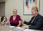 Jasmine Maraldo, center, with daughter 3-year-old Isabella, gets the details of her scholarship from Board Member Tricia Gallenbeck during the Nevada Women's Fund Scholarship distribution, June 20, 2019.