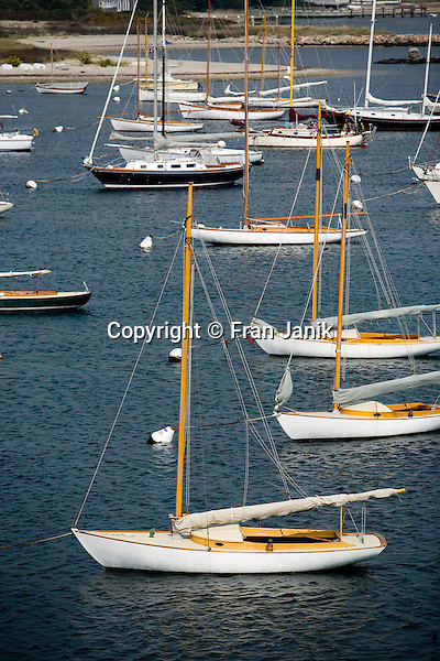 A group of  sailboats rest at anchor in the Vineyard Haven harbor on the island of Martha's Vineyard in the Commonwealth of Massachusetts.