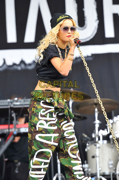 Rita Ora.performing at the Barclaycard Wireless Festival, Hyde Park, London, England. 7th July 2012..music live gig on stage show half length microphone sunglasses singing black beanie hat crop top t-shirt  cropped midriff  slogan writing army green trousers camouflage 3/4 .CAP/MAR.© Martin Harris/Capital Pictures.