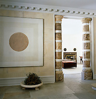 A contemporary painting hangs in the hall with a pair of pillars heralding the entrance to the living room