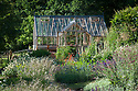 Greenhouse and garden, late June. Planting includes Allium caeruleum, Anthemis tinctoria 'Sauce Hollandaise',  Deschampsia cespitosa 'Goldtau', Geum 'Fire Opal', Knautia macedonica, Sanguisorba officinalis 'Arnhem', Verbascum chaixii 'Album'.