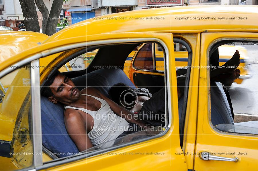 INDIA West Bengal, Kolkata, open garage in Elgin Road , open air repair of a HM Ambassador yellow cab, the car is still produced new at Hindmotor factory after license of Oxford Morris, sleeping mechanic  / INDIEN Westbengalen Kalkutta, offene Kfz Werkstatt in der Elgin Road , Reparatur eines Ambassador Taxi , der HM Ambassador laeuft heute noch neu nach Vorlage des Oxford Morris bei HM Hindustan Motors vom Band, schlafende Monteure