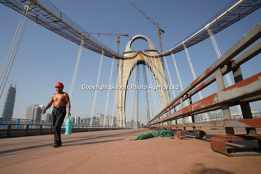 Workers labor on the soon to be completed bridge across the Pearl River in Guangzhou, China..13 Nov 2008