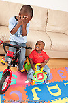 12 month old baby boy on wheeled plastic toy looking at his 3 year old brother on his bicycle with training wheels vertical brother playing peek a boo covering face with hands